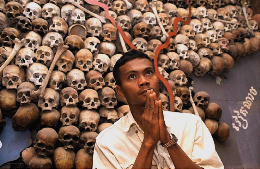 """""""A Cambodian looking skyward in front of skulls placed in the shape of Cambodia.  LF wonders if his prayers relate to what the yanks did that killed millions and then assured the rise of the Khmer Rouge"""""""